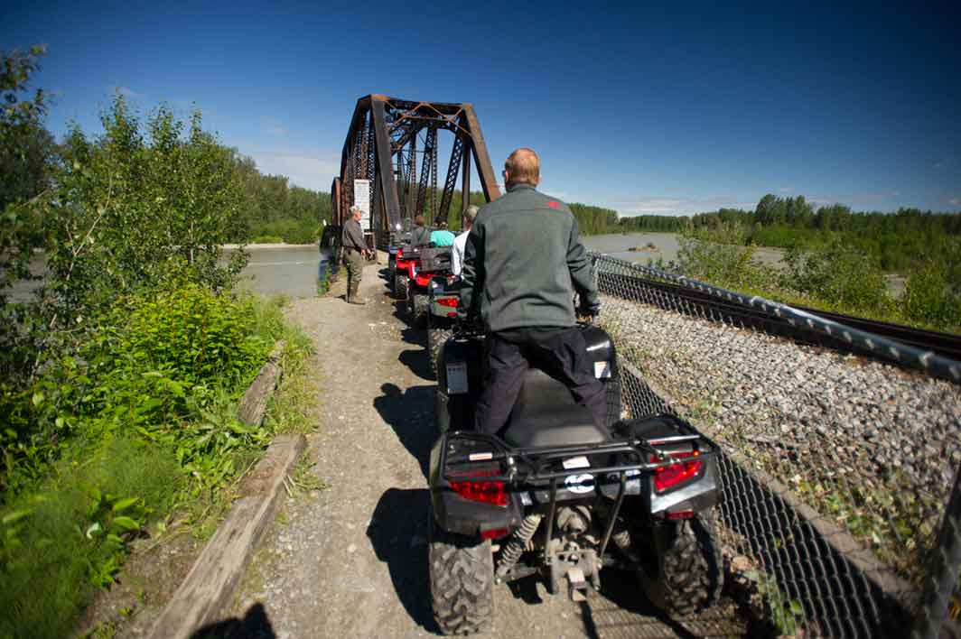 Quads starting across the railroad bridge